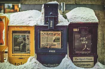 newspaper machines covered in snow