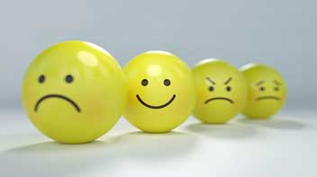 four yellow balls with different emotions written on them, the smiling ball is highlighted