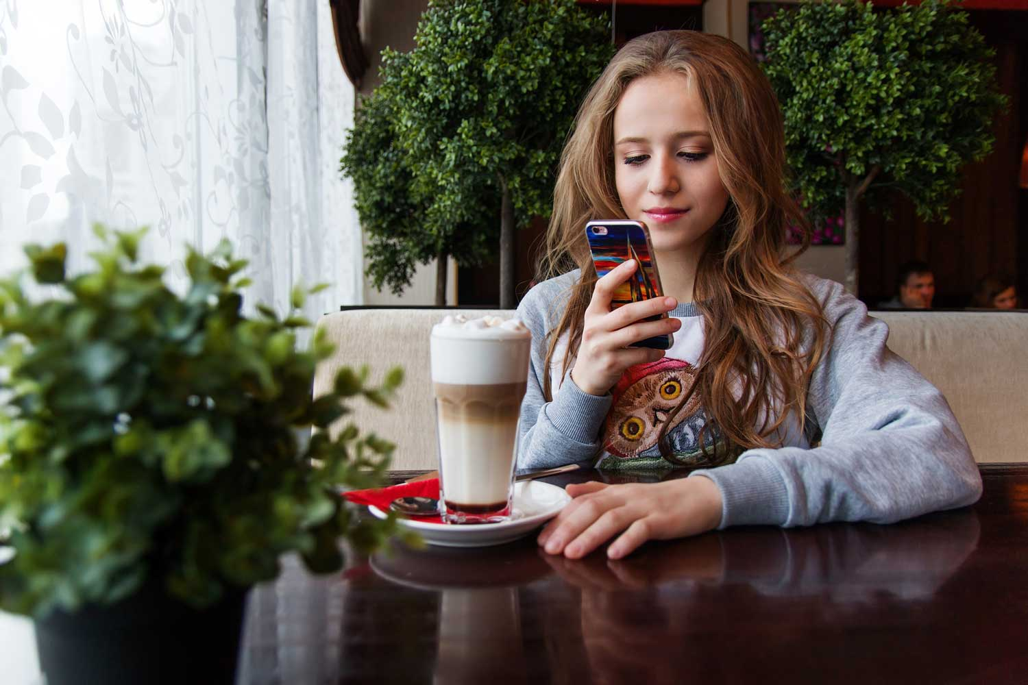 girl at a coffee shop on her phone