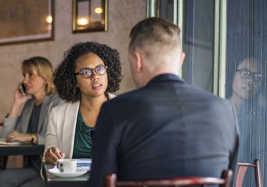 woman looking like she is angry while talking to a man sitting at a coffee place