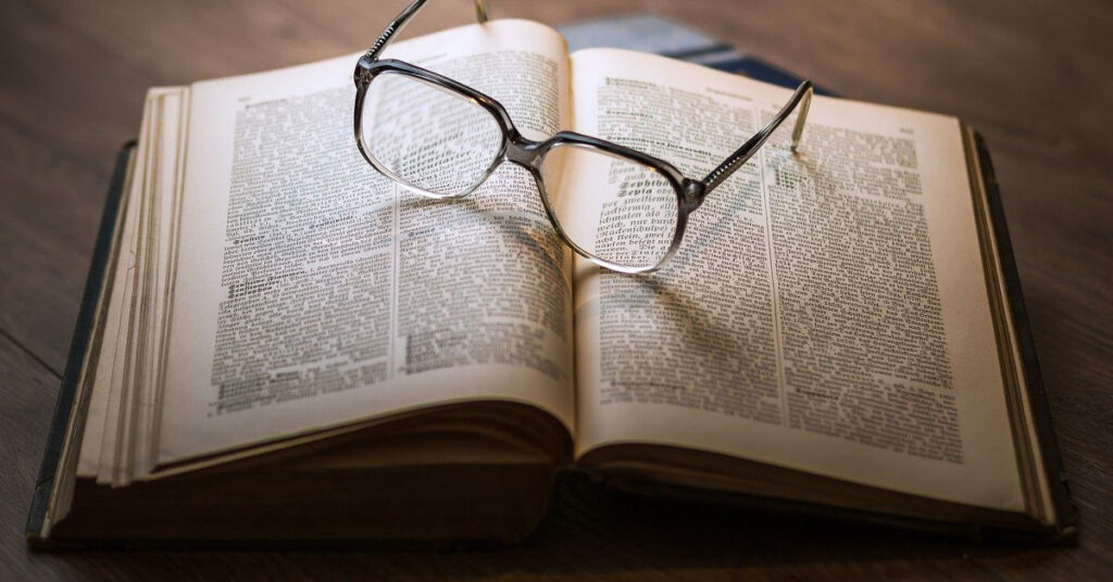 image of an open dictionary with a pair of glasses sitting on top